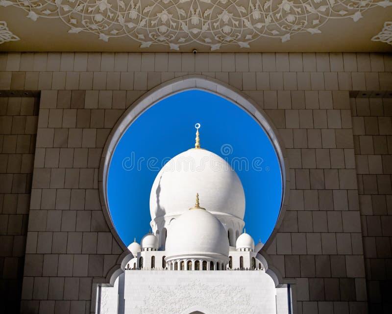 Abóbadas brancas do xeique Zayed Grand Mosque através da porta imagens de stock