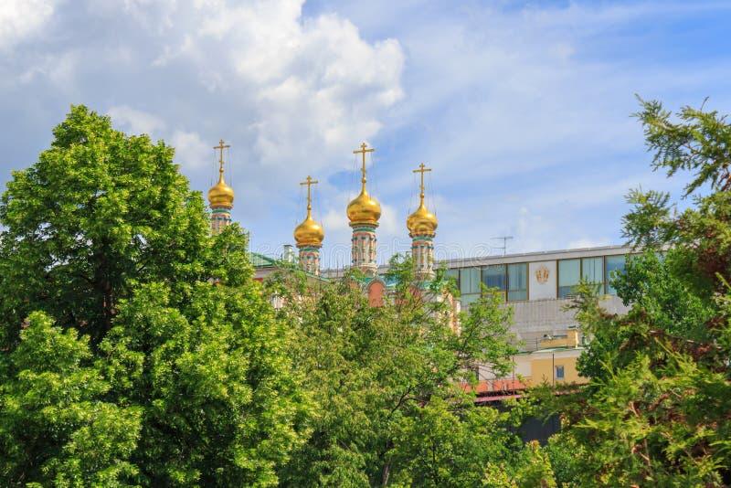 Abóbadas douradas da catedral de Verkhospasskiy no Kremlin de Moscou em um fundo do céu azul no dia de verão ensolarado fotografia de stock