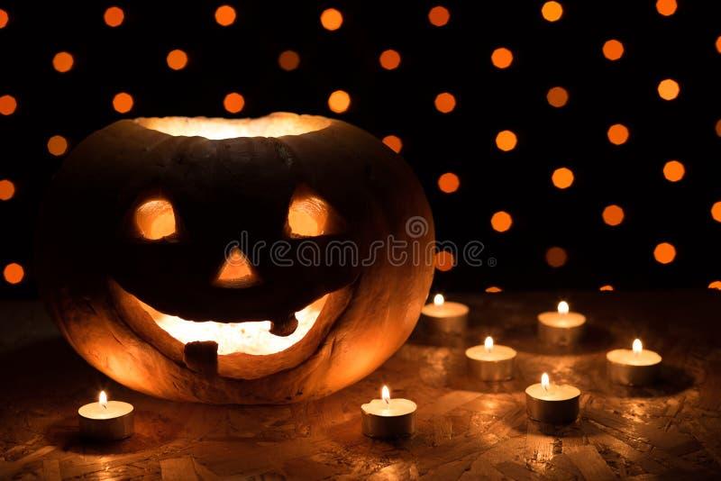 Abóbora alaranjada como uma cabeça com olhos cinzelados e um sorriso com candl foto de stock