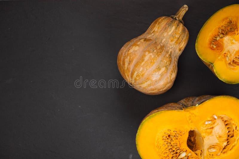 Abóbora alaranjada cortada no prato branco no fundo de pedra preto fotografia de stock