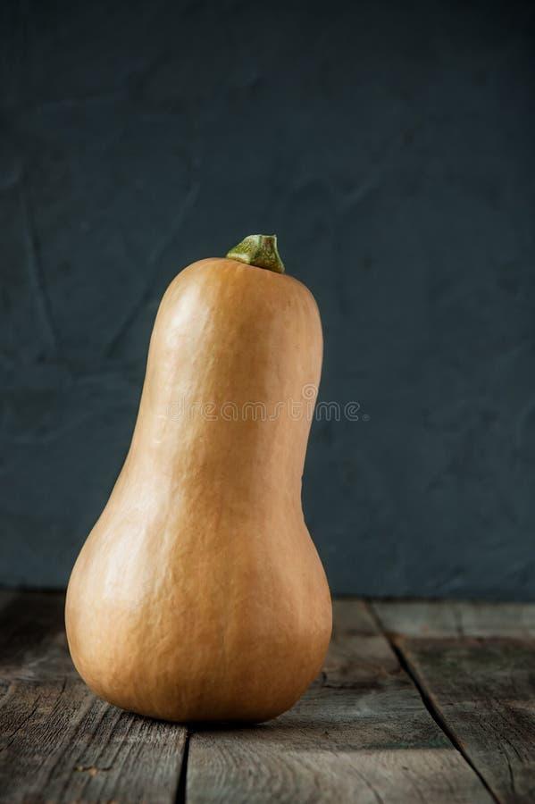 Abóbora alaranjada madura que stading na tabela de madeira rústica no fundo de pedra escuro Vegetariano, colheita do outono, ação fotos de stock