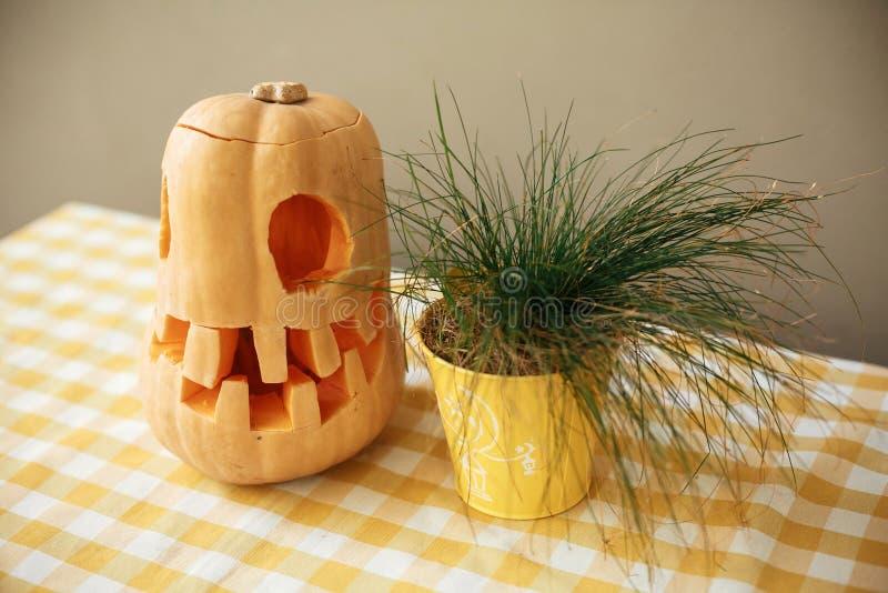 Abóbora com cara assustador e planta na tabela na rua da cidade, decoração do feriado do café e construções Decoração da rua de D fotos de stock