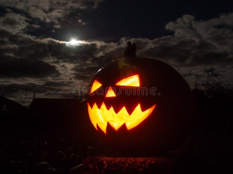 Abóbora de Dia das Bruxas com olho fumarento e a Lua cheia foto de stock