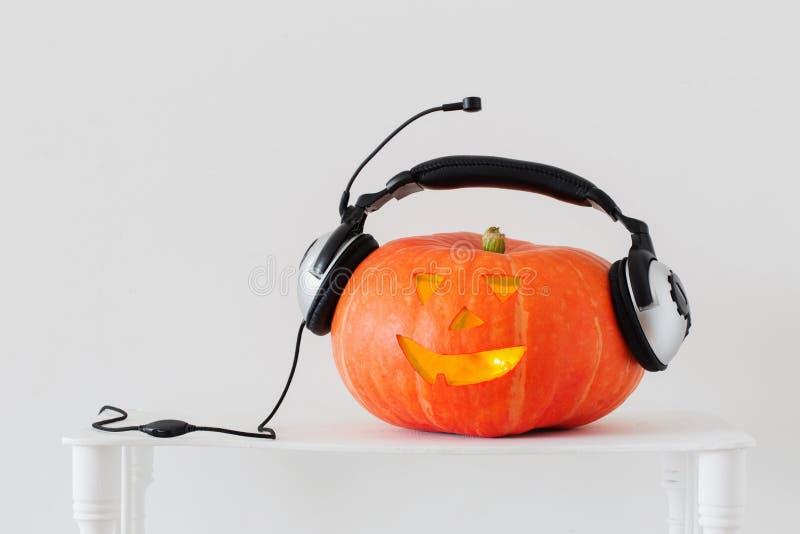 Abóbora de Dia das Bruxas com os fones de ouvido no fundo branco imagens de stock royalty free