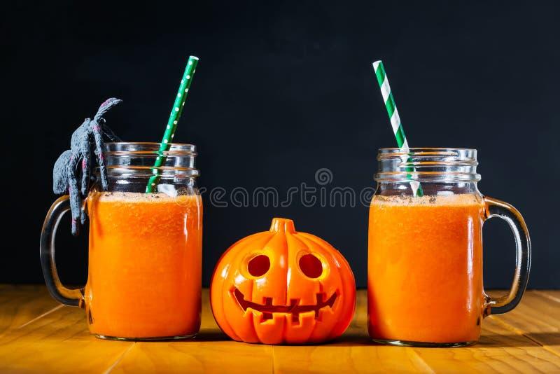 Abóbora de Dia das Bruxas com suco de cenoura em uns frascos de pedreiro fotografia de stock royalty free