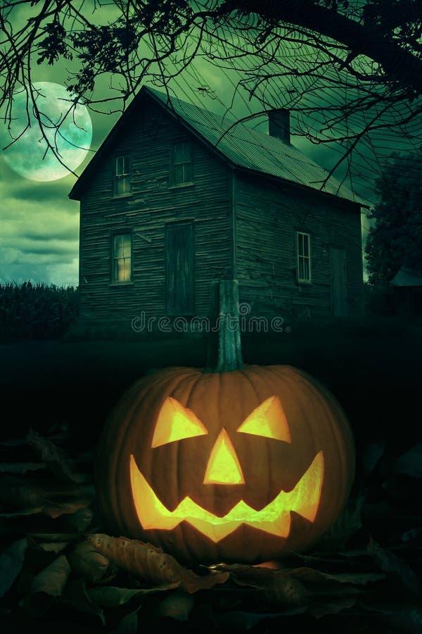 Abóbora de Halloween na frente de uma casa assustador imagens de stock royalty free