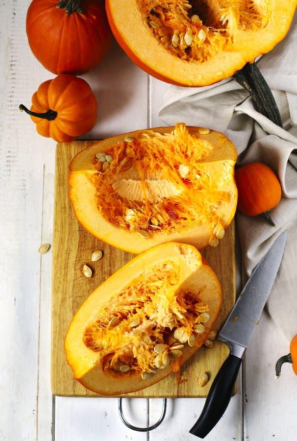 Abóbora desbastada na placa de corte com faca de cozinha fotografia de stock royalty free