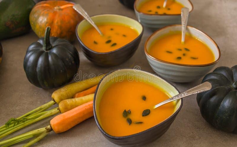 Abóbora e cenoura em umas bacias de sopa cerâmicas decoradas com sementes de abóbora, fotografia de stock