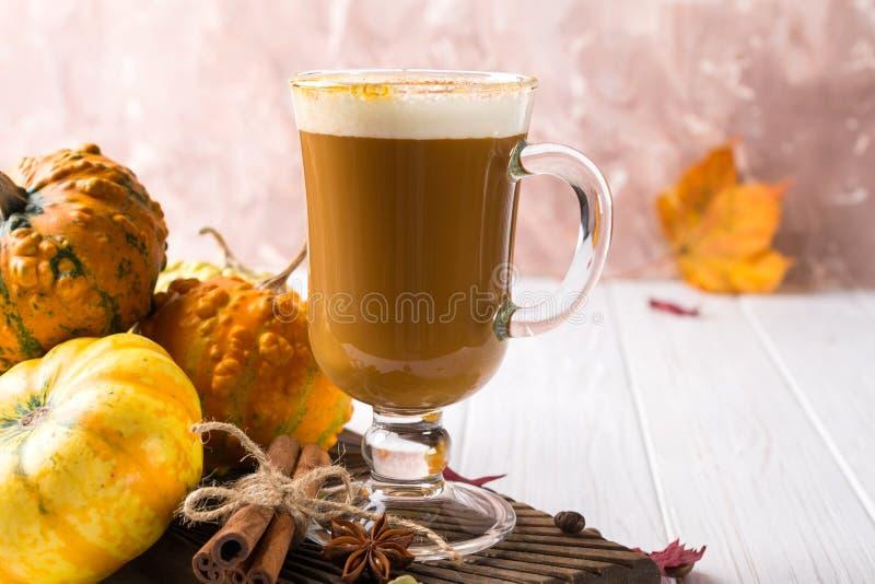 A abóbora temperou o latte ou o café no copo de vidro, seca as folhas Bebida quente tradicional do outono ou do inverno fotografia de stock