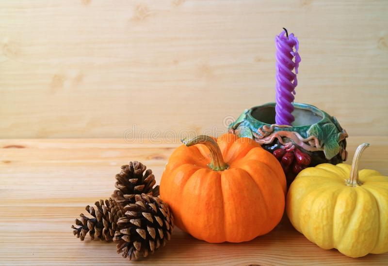 Abóboras maduras da cor amarela e alaranjada com os cones secos naturais do pinho e vela roxa no castiçal do motivo da uva fotografia de stock royalty free
