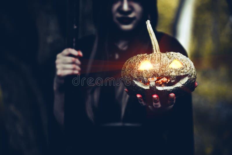 Ab?bora na m?o da bruxa Ab?bora da terra arrendada da mulher adulta no dia de Dia das Bruxas da floresta e no conceito escuros do imagens de stock