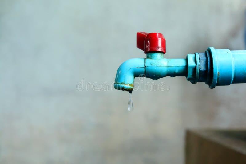 A aba velha da água azul tem o gotejamento da água para fora, água da falta do conceito no mundo para o dia da água fotografia de stock