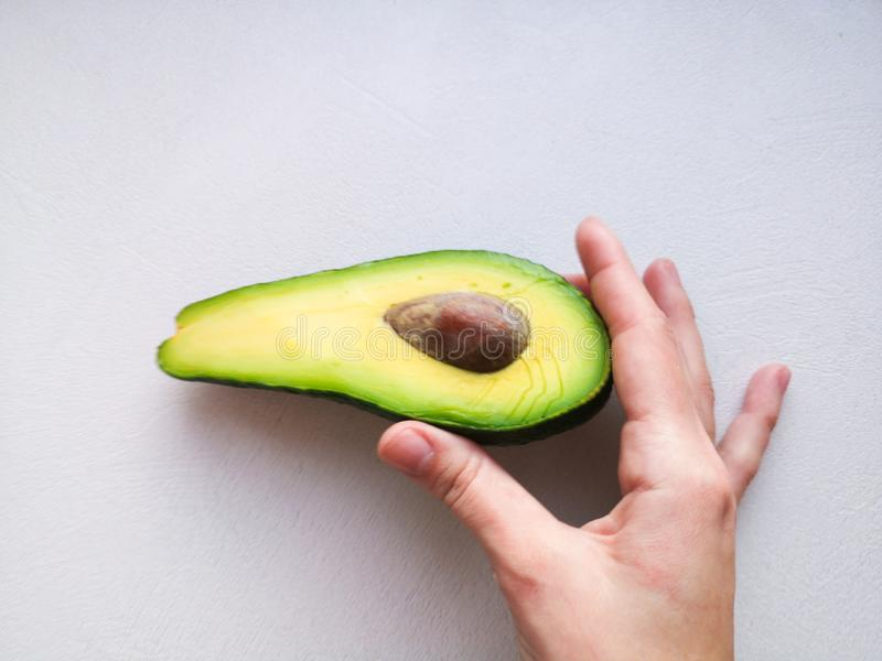 Abacate à disposição, no fundo branco Homem que propõe à mulher com acoplamento Ring In Avocado closeup Corte o abacate fotografia de stock