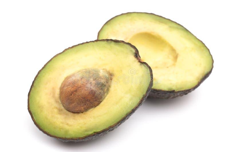 Abacate cortado com seu poço no fundo branco imagem de stock