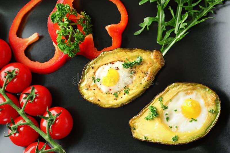 Abacate cozido com ovos e vegetais na placa, close up imagem de stock