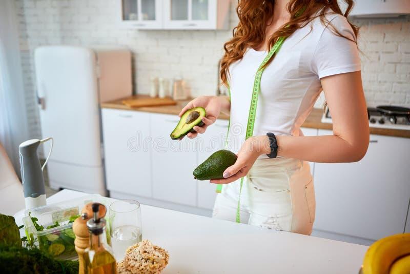 Abacate feliz novo da terra arrendada da mulher para fazer a salada na cozinha bonita com os ingredientes frescos verdes dentro a fotografia de stock royalty free