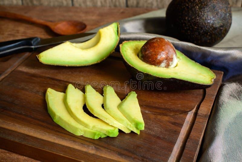 Abacate maduro da fatia na placa de corte de madeira fotos de stock