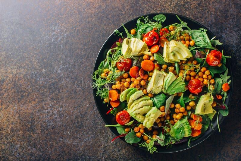 Abacate, tomate roasted, verdes e salada dos grãos-de-bico fotografia de stock royalty free