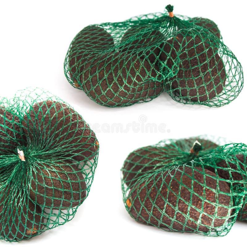 Abacates orgânicos frescos em um saco de corda verde em um fundo branco isolado, colagem dos hass do alimento, espaço da cópia fotografia de stock royalty free