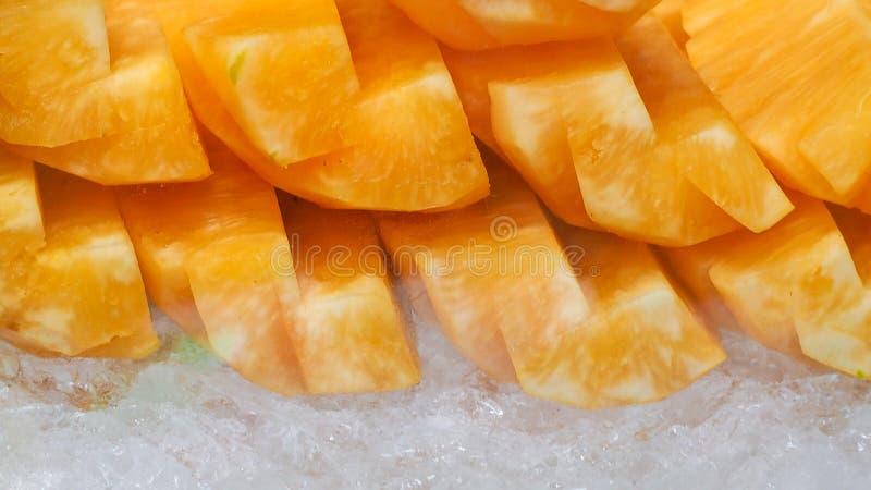 Abacaxi alaranjado ou amarelo cortado no gelo esmagado Fruta tropical Petisco saudável Enzima da bromelina extraída do abacaxi fo imagens de stock
