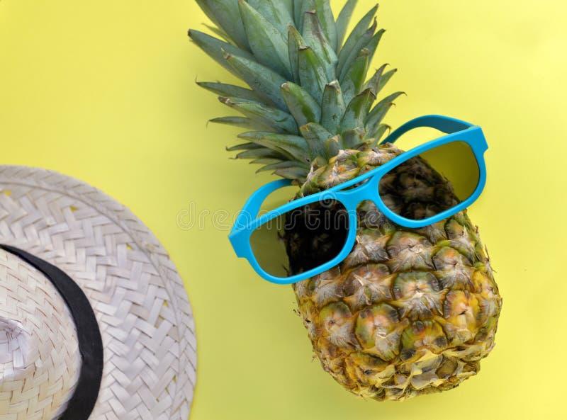 Abacaxi com óculos de sol e o chapéu de palha azuis no fundo amarelo fotos de stock royalty free