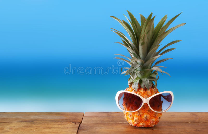 Abacaxi com os óculos de sol na tabela Praia e tema tropical fotografia de stock