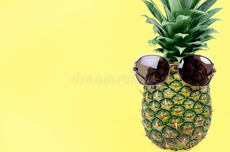Abacaxi com os ?culos de sol no fundo amarelo foto de stock royalty free