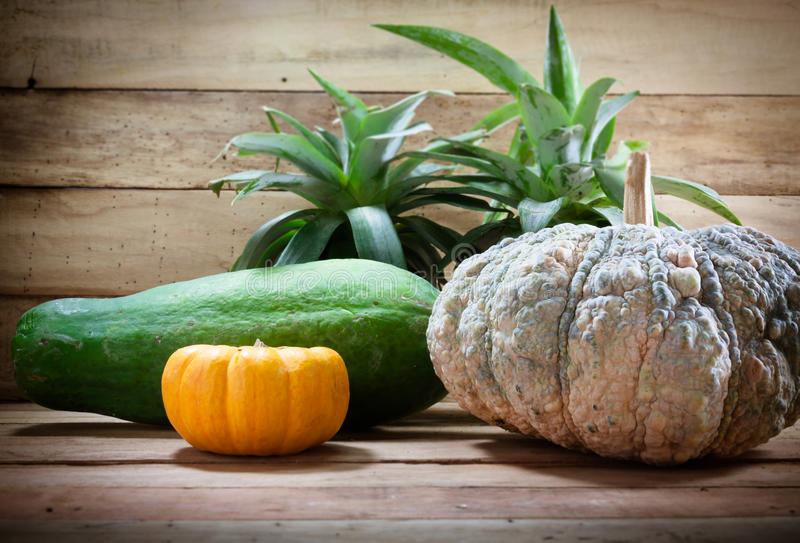 Abacaxi do foco seletivo, abóbora, papaia na madeira fotos de stock