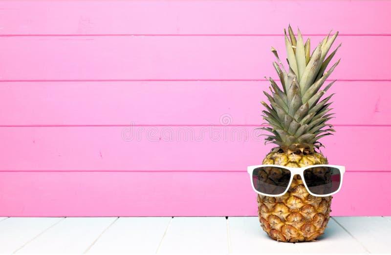Abacaxi do moderno com os óculos de sol contra a madeira cor-de-rosa foto de stock