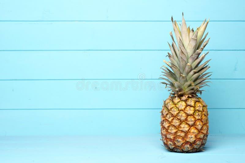 Abacaxi em um fundo de madeira azul pastel foto de stock royalty free