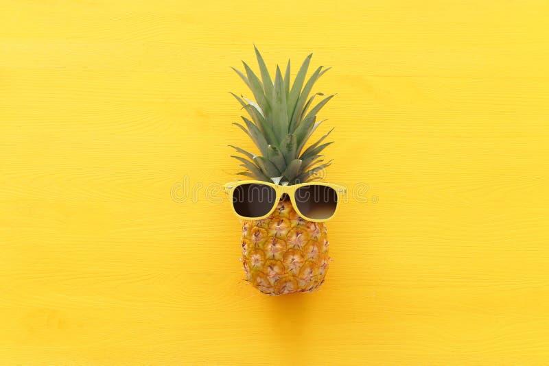 Abacaxi maduro em óculos de sol à moda sobre o fundo amarelo de madeira Conceito tropical das f?rias de ver?o Vew superior imagem de stock royalty free