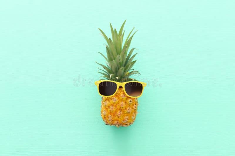 Abacaxi maduro em óculos de sol à moda sobre o fundo azul de madeira Conceito tropical das f?rias de ver?o Vew superior fotografia de stock