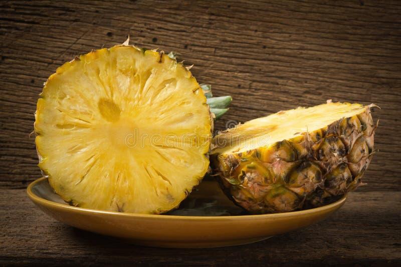 abacaxi no prato meio na madeira velha foto de stock