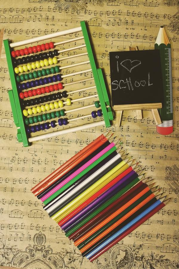Old school stuff on the stamp paper. Abacus,chalk board ,pencil with ` I love school ` message . Old paper background stock photo