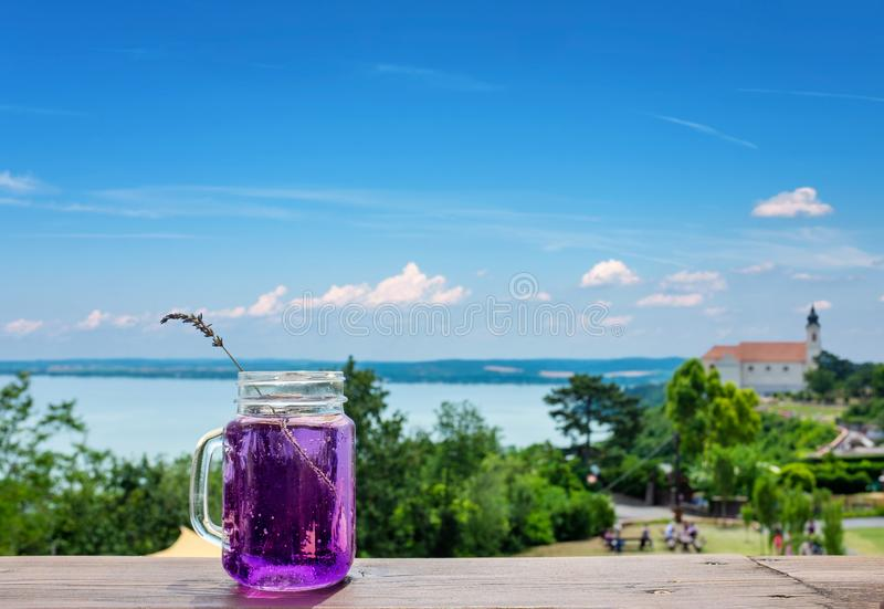 Abadia de Tihany com o lago Balaton no fundo e uma bebida da alfazema focalizada na parte dianteira imagens de stock royalty free
