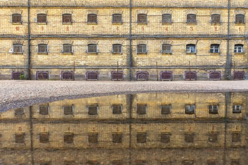 Abadondes jail brick wall and cell windows with bars, prison wall reclection in water on ground after rain royalty free stock photos