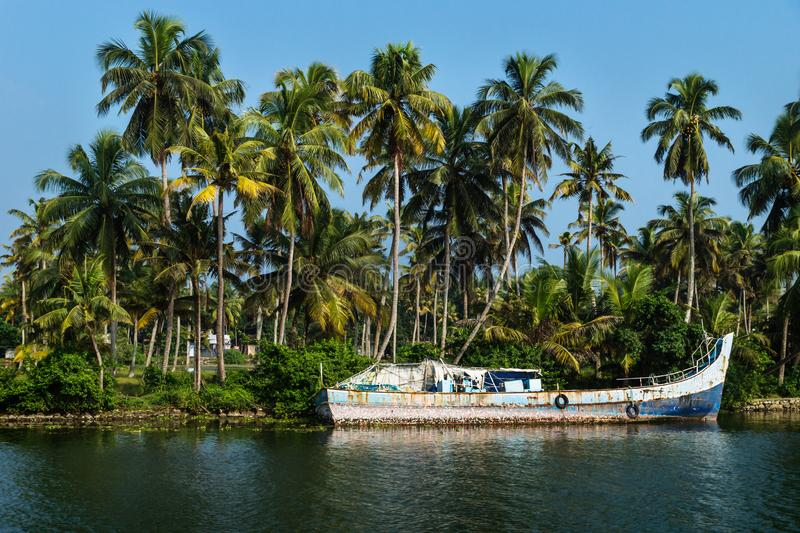 Abadoned ocean fishing boat along the canal Kerala backwaters shore with palm trees between Alappuzha and Kollam, India. Abandoned ocean fishing boat along the stock image