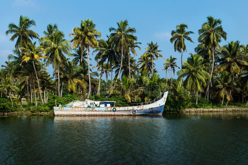 Abadoned ocean fishing boat along the canal Kerala backwaters shore with palm trees between Alappuzha and Kollam, India. Abandoned ocean fishing boat along the royalty free stock images