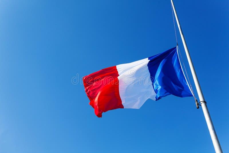 Abaissé au drapeau de moitié-personnel de la France au-dessus du ciel bleu image stock