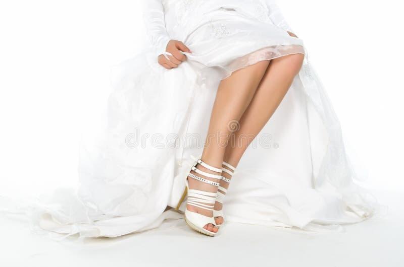 Abaissez la section des jambes de la jeune mariée avec les talons blancs images libres de droits