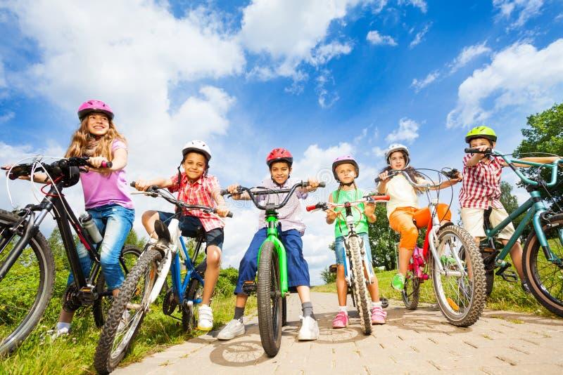 Abaixo da opinião de ângulo as crianças nos capacetes com bicicletas imagem de stock