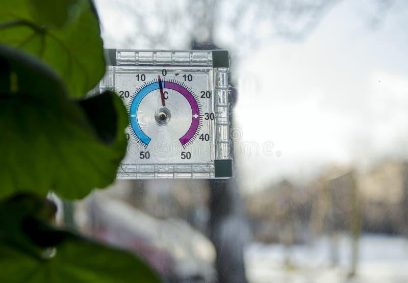 Abaixo de zero no termômetro análogo, o termômetro fora da janela, geada pequena no ar livre foto de stock