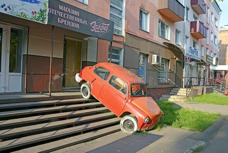 Abakan, Rusland 07 18 2019: Vreemd/onbegrijpelijke advertentie grappige boekhandel De oude auto is geïnstalleerd op de treden die stock afbeeldingen
