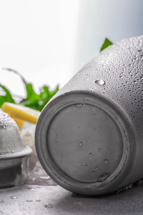 Abanador úmido metálico de prata isolado em um fundo branco borrado, em uma hortelã fresca e em um limão suculento em um tabela-p imagem de stock royalty free