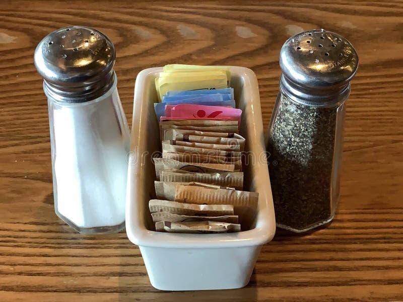 Abanadores de sal e de pimenta com um recipiente do açúcar e do substituto do açúcar imagens de stock royalty free