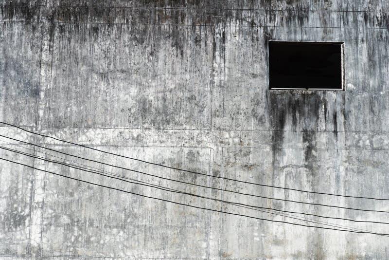 Abandon grunge grey cement wall with black dark window urban building background. Abandon grunge grey cement wall texture with black dark window urban building stock images