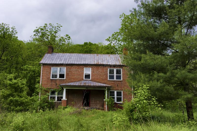 Abandoned Brick home in Virginia. In the Appalachian Mountains in Virginia stands an abandoned brick home decaying due to the natural elements royalty free stock photography