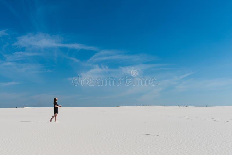 Abandone com areia e a fêmea brancas no preto imagem de stock