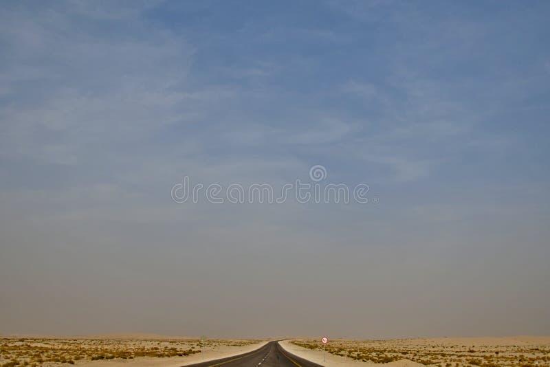 Abandone el camino de la carretera en la Arabia Saudita que conduce en el desierto imagenes de archivo