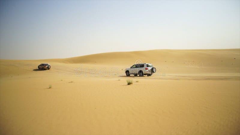 Abandone el safari SUVs que golpea a través de las dunas de arena árabes Viaje de SUV a través del desierto árabe foto de archivo